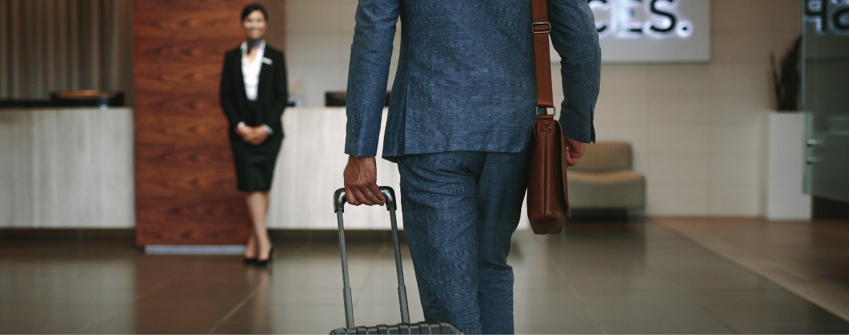 A man walks to a hotel receptionist with luggage in hand